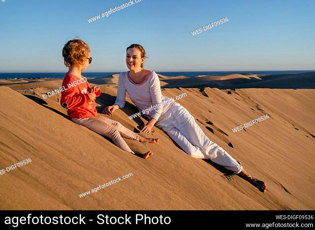 Happy mother and daughter relaxing in sand dunes, Gran Canaria, Spain