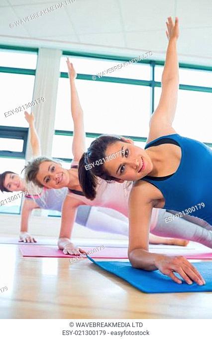 Happy women in side plank yoga pose in fitness studio