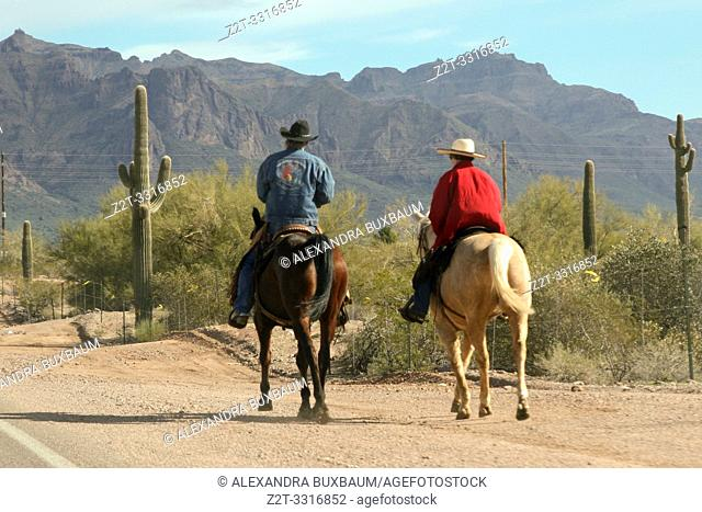 Men riding horseback along a road in Arizona