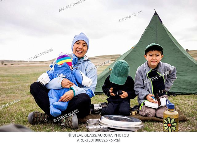 A family consisting of a Japanese American woman holding her 6 month baby girl, and 4 year old and 6 year old Japanese American boys sit in front of their tent...