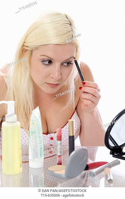 Young woman putting on makeup using eye brow pencil