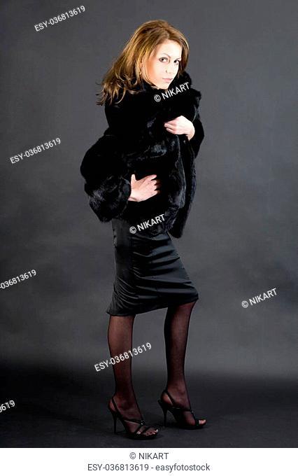 The young beautiful girl in a black mink fur coat