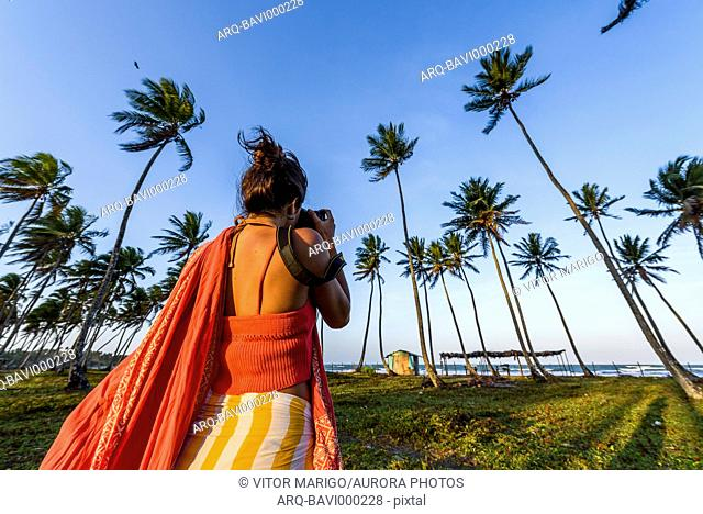 Rear view of female photographer in tropical scenery with coconut palm trees, Boipeba Island, south Bahia, Brazil