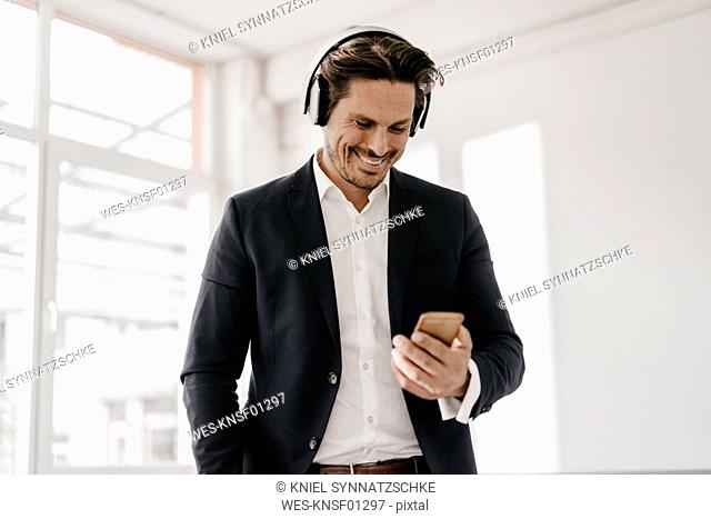 Smiling businessman with cell phone and headphones