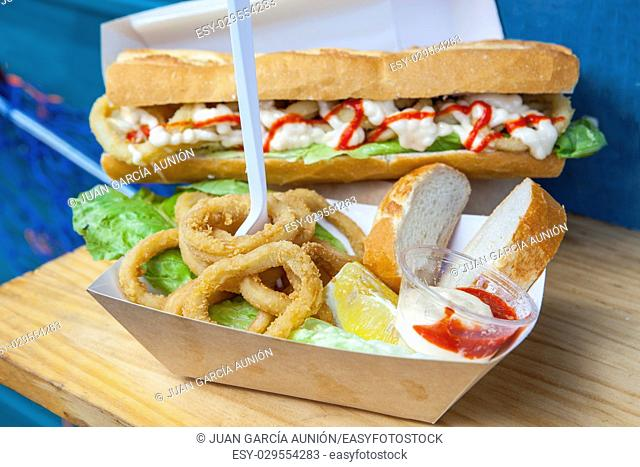 Fried squid rings displayed on bread roll and cardbox. Popular spanish snack
