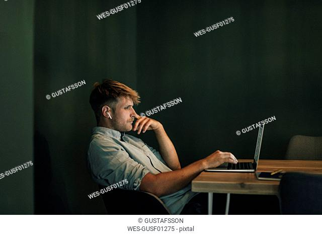 Man sitting in office, working late in his start-up company, listening music