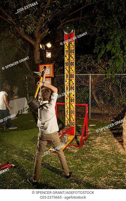 A teen boy swings a mallet at a strength machine during an evening Harvest Fair at a private school in Lake Forest, CA