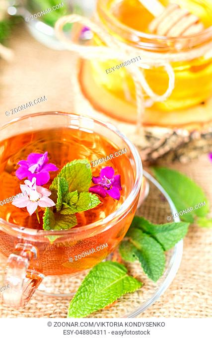 Glass cup of summer herbal tea with fresh mint and field larkspur. Jar of honey. Wooden table. Shallow depth of field