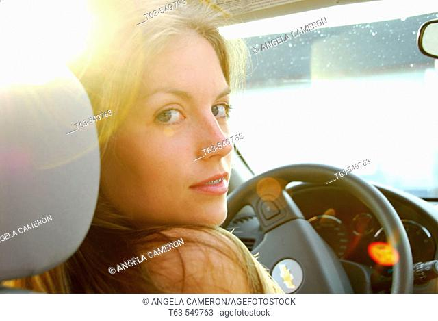 girl 18 yrs old driving car with evening sun peeking through