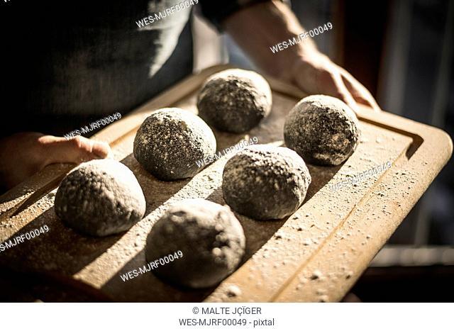 Man preparing black burger buns in kitchen, letting dough rise