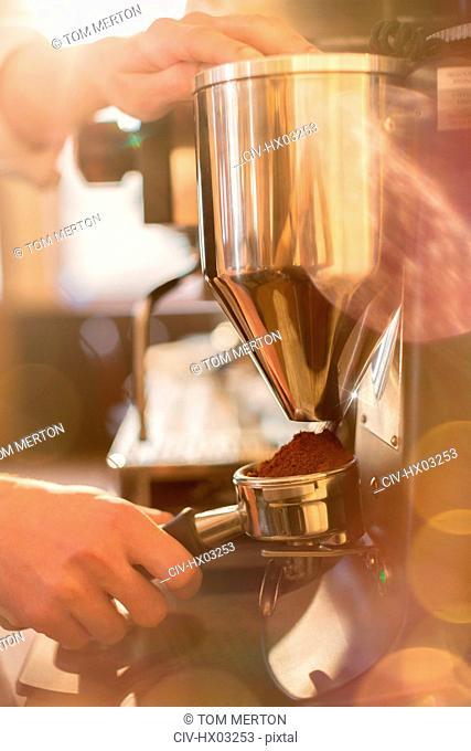 Close up barista using espresso machine grinder