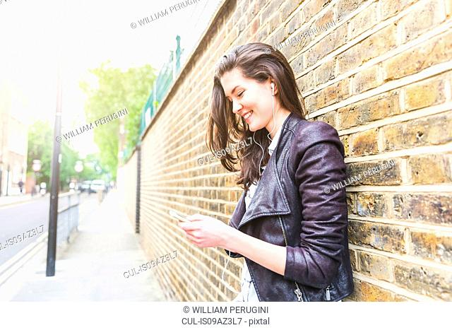 Young woman leaning against brick wall texting on smartphone