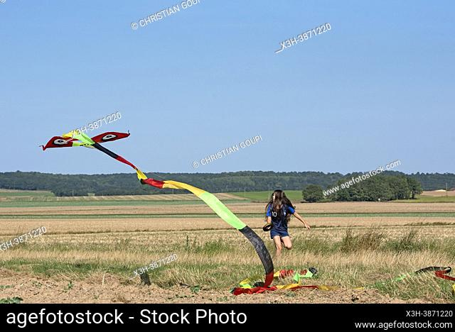 Young girl in denim shorts and blue shirt flying a Chinese kite in a flat landscape in Centre-Val de Loire region, France