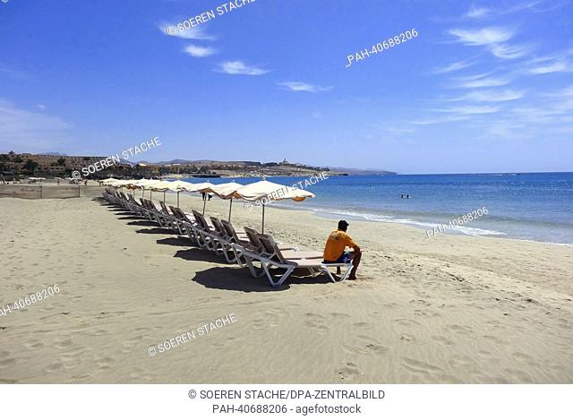 A man sits on a deckchair and waits for customers at the sandy beach of Costa Calma on Fuerteventura, Spain, 05 June 2013