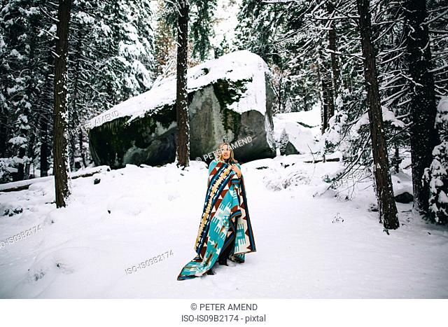 Woman in snow-covered forest wrapped in blanket