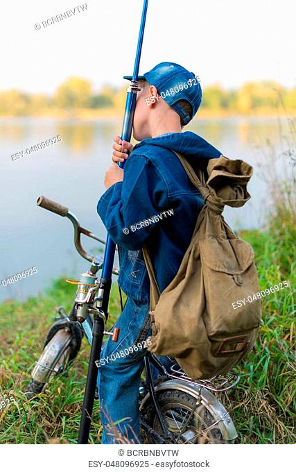 A child on a bicycle with a backpack on the shore of the river with fishing accessories