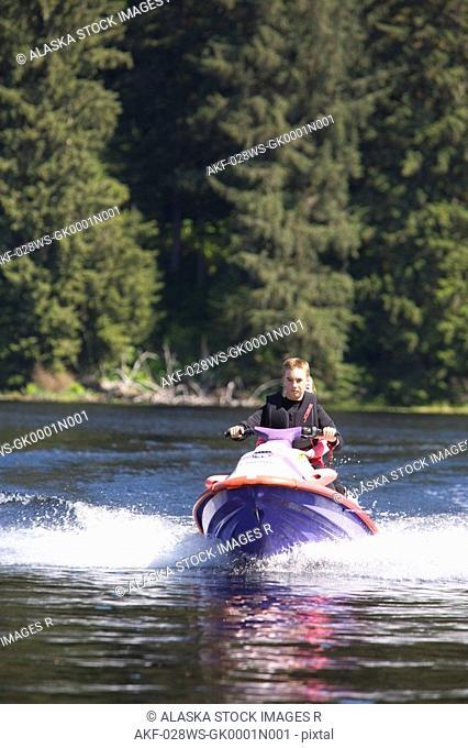 14 year old boy driving a jetski at Auke Lake north of Juneau southeast Alaska summer