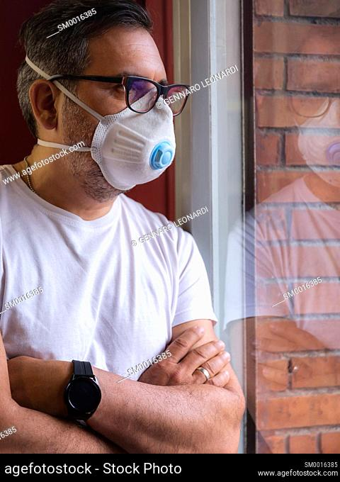 A man with a protective medical mask waits for the end of the covid-19 emergency quarantine, behind the glass of his home window