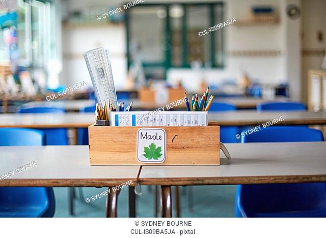 Classroom desk with wooden box full of pencils and rulers in primary school classroom
