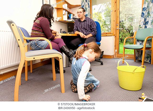 Child playing with toys while her mother talks to a GP doctor, United Kingdom, Europe