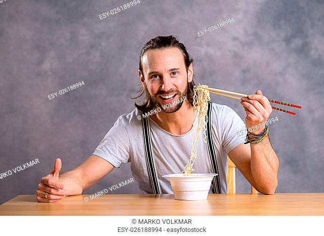young man eating asian food and smiling in to the camera