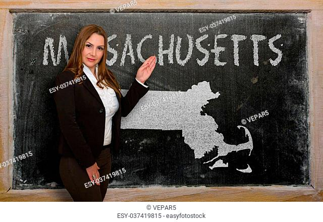 Successful, beautiful and confident young woman showing map of massachusetts on blackboard for presentation, marketing research and tourist advertising