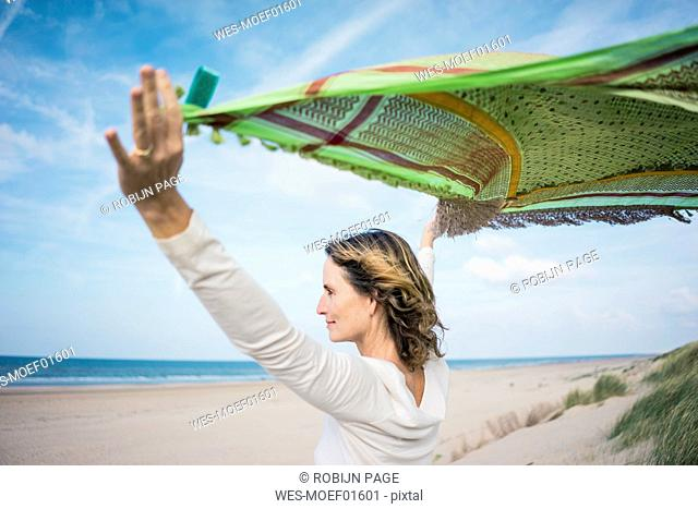 Mature woman holding flapping scarf in the wind, relxiang in the dunes