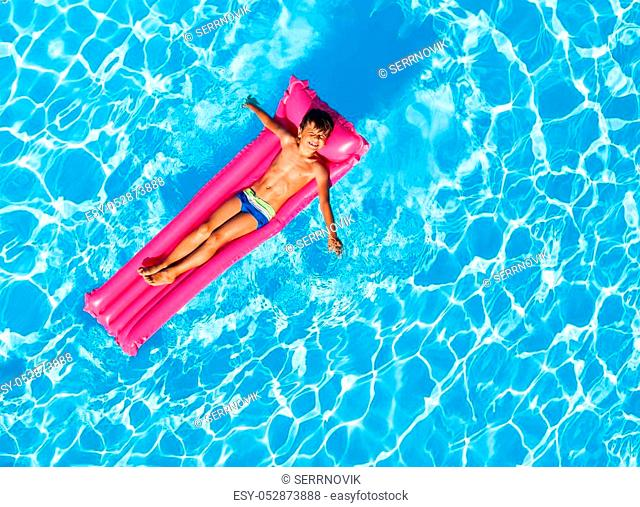 Top view portrait of cute boy swimming on pink inflatable mattress on transparent water surface with copy-space