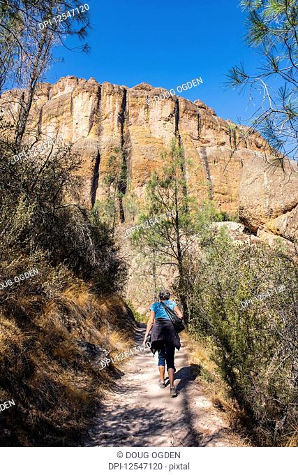 A woman walking up the Balconies Cave trail below massive cliffs in the Pinnacles National Park; California, United States of America