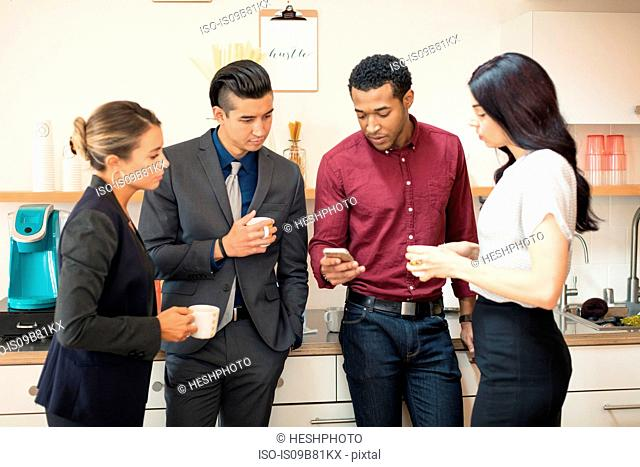 Businesswomen and men looking at smartphone in office kitchen