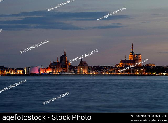 29 August 2020, Mecklenburg-Western Pomerania, Stralsund: The evening silhouette of the city behind the Strelasund with the buildings at the harbour