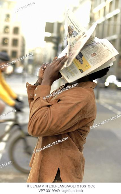 African man with newspaper on face, at street in city, in Frankfurt, Germany