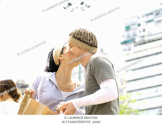 Young woman holding shopping bag and kissing young man on cheek
