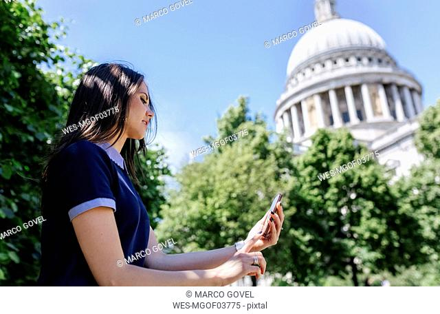 UK, London, young woman using her smartphone near St. Paul's Cathedral