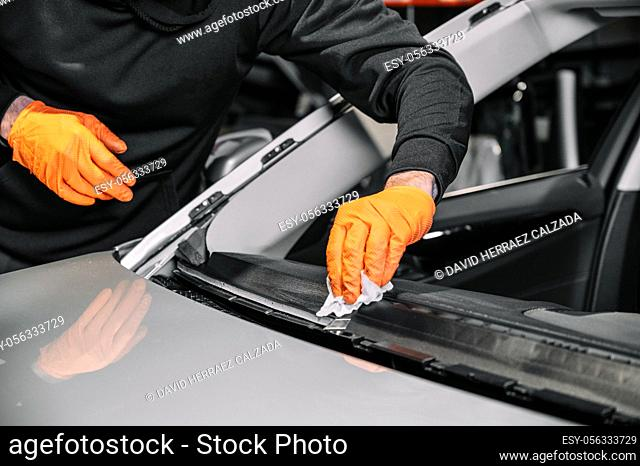 Close up, Car glazing, fixing and repairing a windshield. Windscreen replace process of a car at a garage service. Cleaning a dashboard