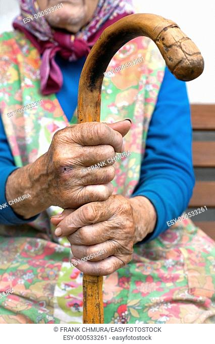 hand of an old peasant woman holding a walking stick