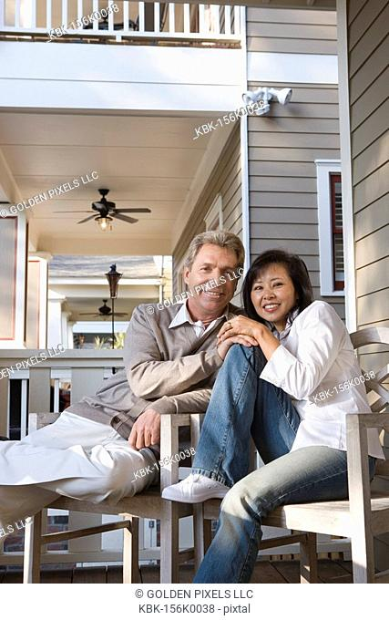 Portrait of an inter-racial couple sitting on the front porch