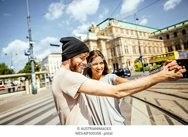 Austria, Vienna, happy young couple dancing Viennese waltz in front of state opera