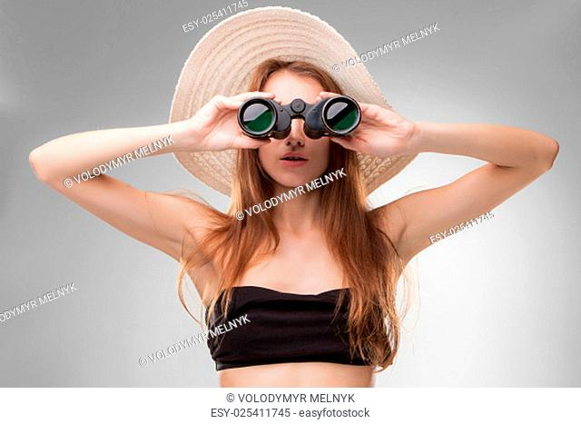 Young woman in hat with binoculars isolated on gray background. Travel and adventure concept. Closeup