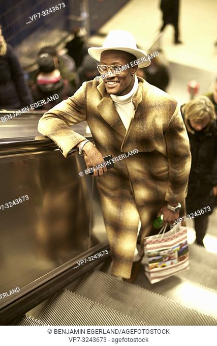 well-dressed man standing on escalator, city life, smiling, in Munich, Germany