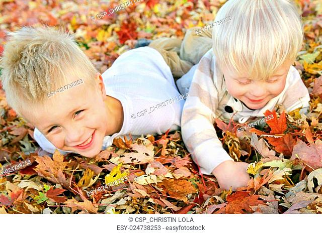 Two Young Children Playing in Fall Leaf Pile