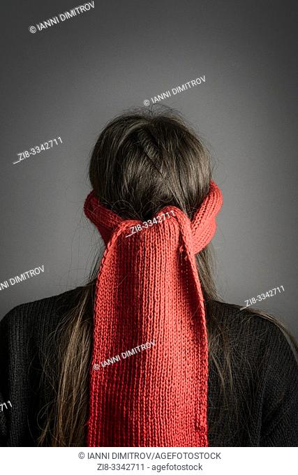 Girl with dark long hair blindfolded with a red knitted scarf- back view