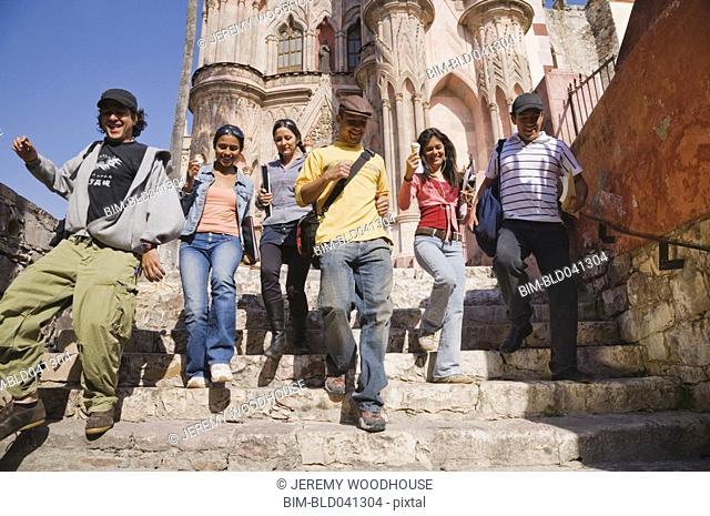 Hispanic college students walking down steps