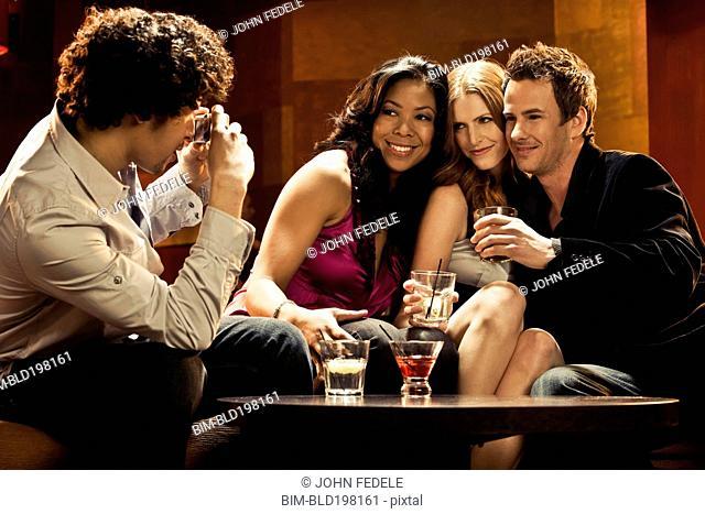 Man taking photograph of friends in nightclub