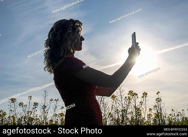 Silhouette mature woman using smart phone while standing against sky at sunset