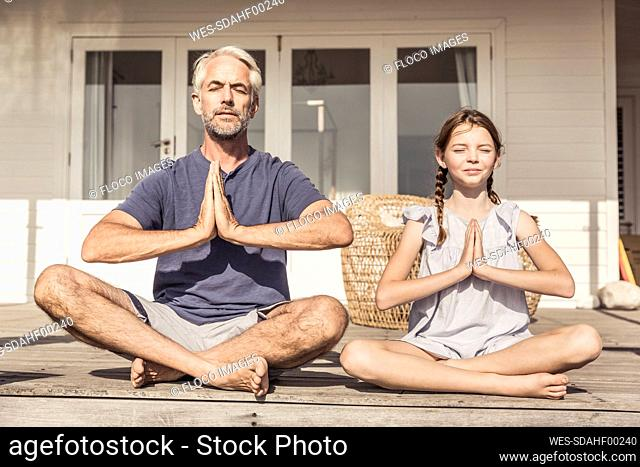 Father and daughter sitting on terrace in sunshine doing yoga