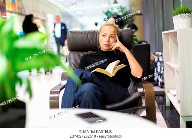 Thougtful woman sitting by wooden table and reading book in public library