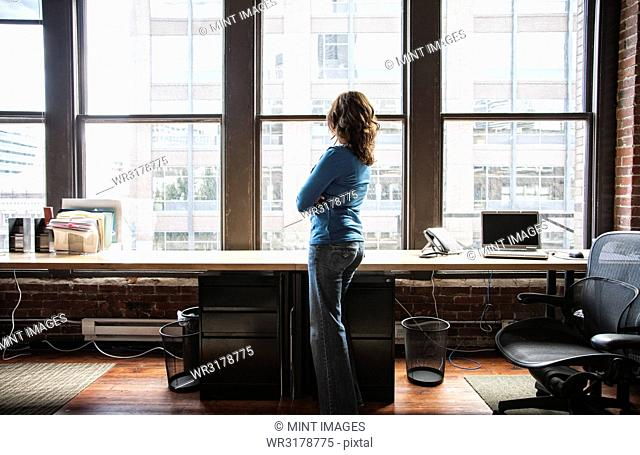 Caucasian woman at office workstation near a large bank of windows