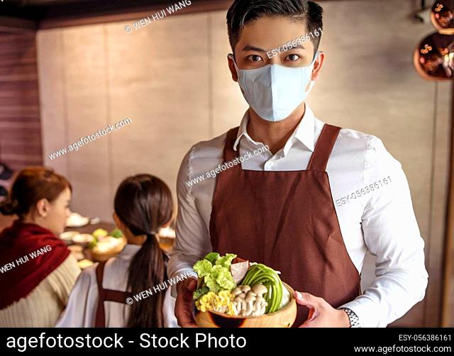 Young waiter wearing protective face mask while serving food to customer in restaurant