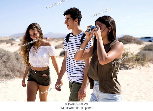 Friends walking on the beach, talking